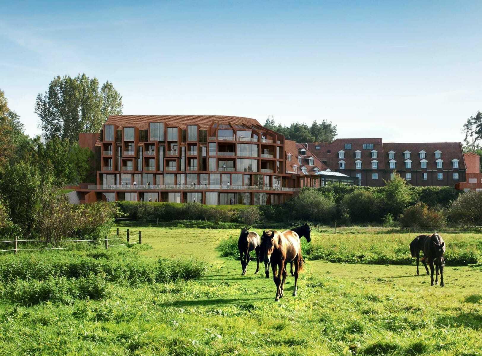 Hotelansicht mit Pferden im Vordergrund