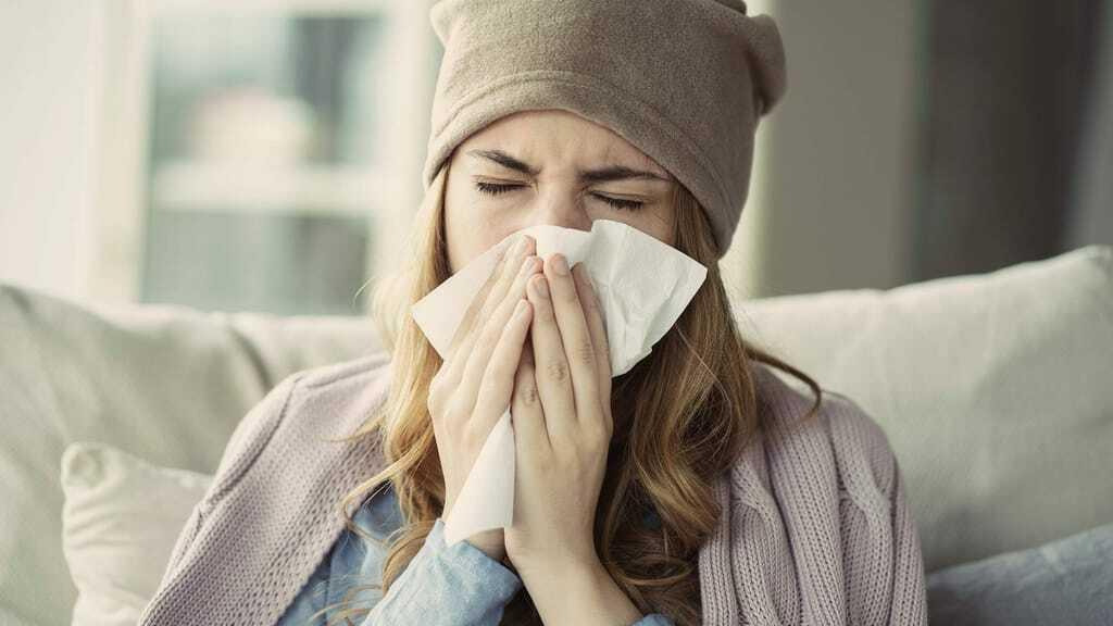 Frau mit Erkältung auf einem Sofa