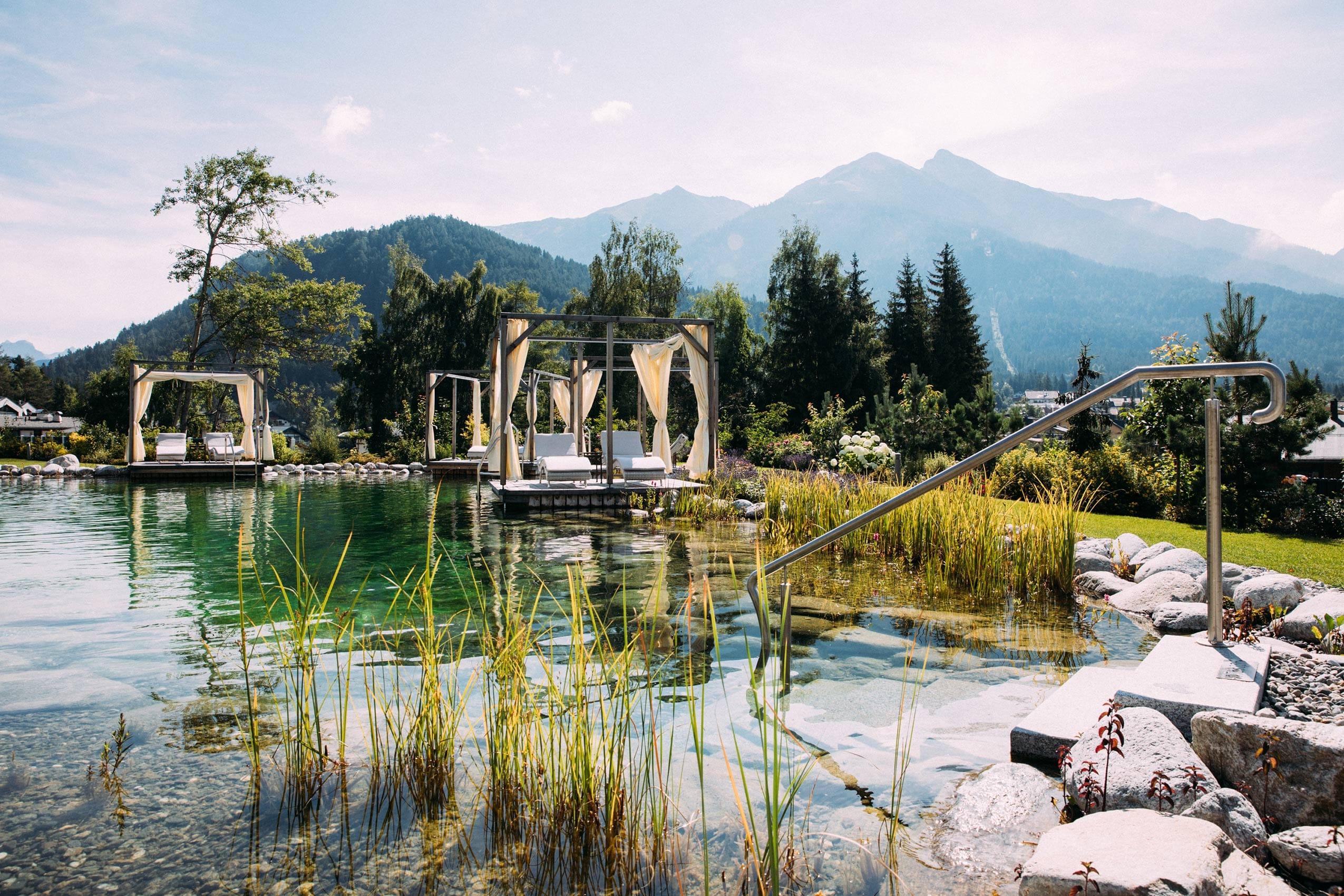Der idyllische Naturbadesee des ASTORIA RESORT in Seefeld bietet einen unverbauten Weitblick auf das Karwendelgebirge.