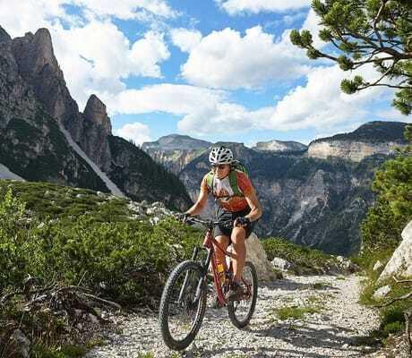Mann macht Fahrrandtour bei sonnigem Wetter in den Bergen_Excelsior_Dolomites_Life_Resort_St_Vigil