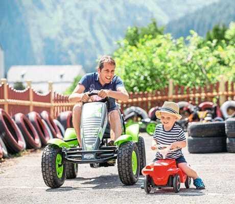 Vater auf einem Go-Kart und kleiner Sohn im Bobbycar_Kaiserhof_Berwang