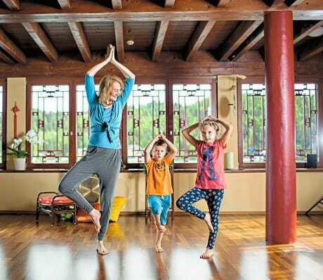 Mutter macht mit ihren zwei kleine Kindern Yoga_Hochschober_TurracherHoehe