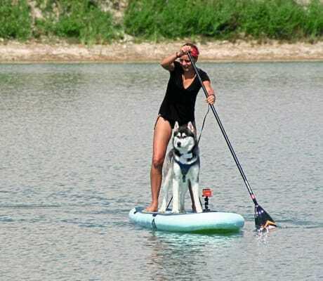 Frau mit Hund auf einem StandupPadel_GutshotelFeuerschwendt_Neukirchen