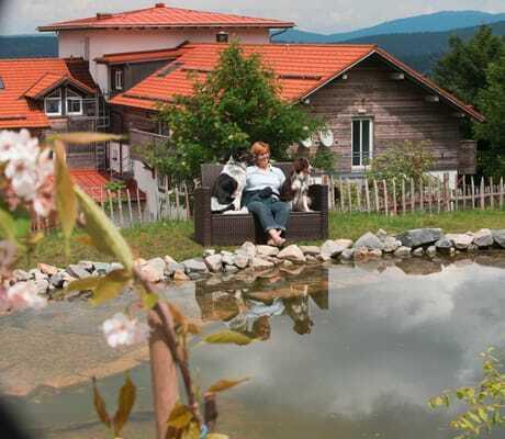 Frau mit zwei Hunden an einem TeichHaus _Waldeck_Philippsreut-Mitterfirmiansreut
