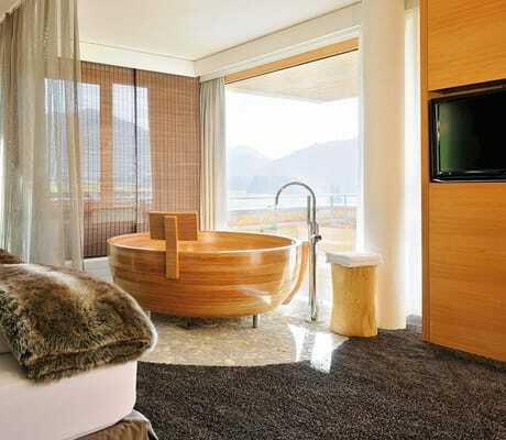 Bild in ein Zimmer mit Badewanne vor dem Fenster_HubertusAlpinLodgeSpa_Balderschwang