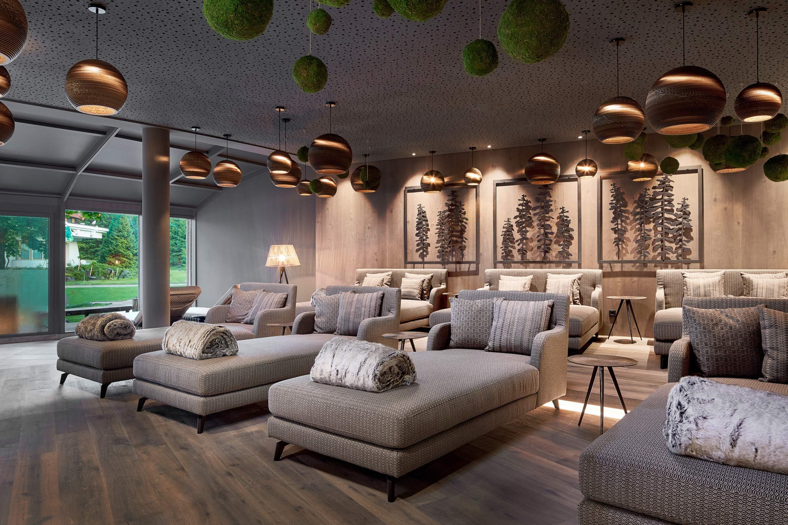 Der stylische Ruheraum in Krumers Alpin Hotel & Spa punktet mit seinen schicken Liegen und dem Ausblick in den Garten.