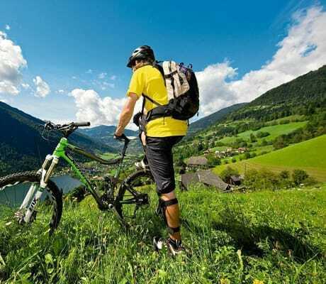 Mann mit seinem Fahrrad in den Bergen_Familien_Sporthotel_Brennseehof_Feld_Am_See
