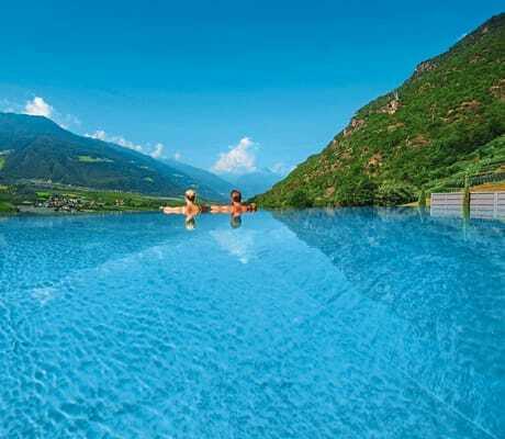 Pärchen blickt vom Infinity Pool aus auf die Berglandschaft_Preidlhof_Luxery_DolceVita_Resort_Naturns