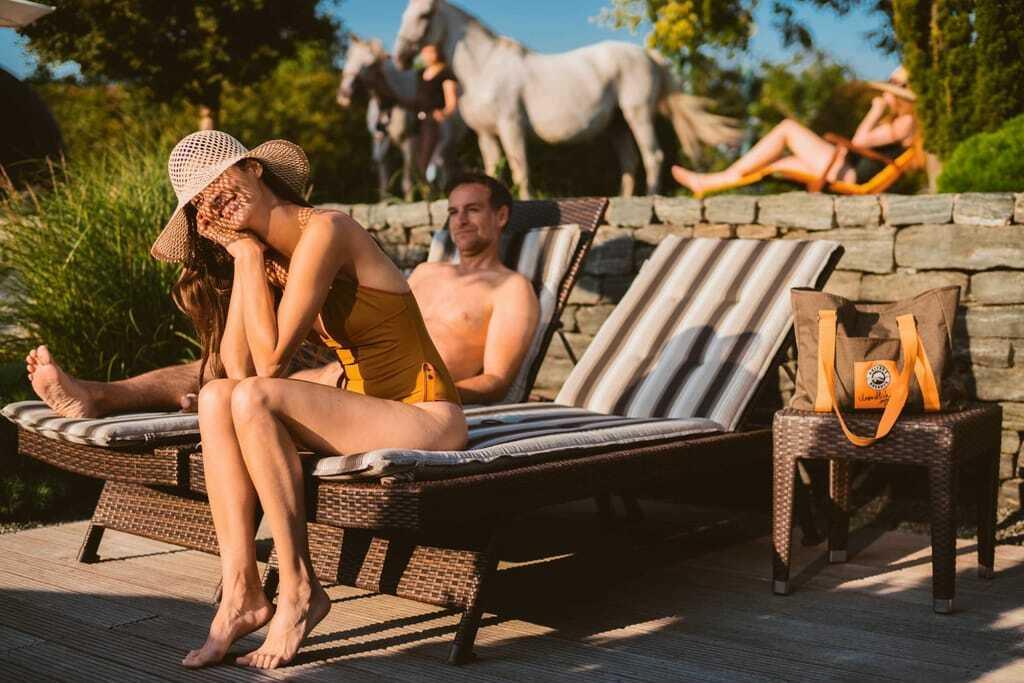 Liegen am Pool mit Pferden im Hintergrund