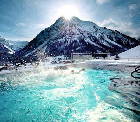 Pool mit Aussicht auf verschneite Berge_Kleinwalsertaler_Rosenhof_Mittelberg