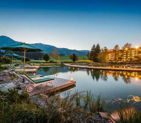 Schwimmsee mit Liegen und Hotelansicht