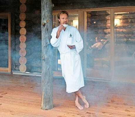 Mann steht an eine Pfahl gelent vor der Sauna_HotelBornmühle_GroßNemerow
