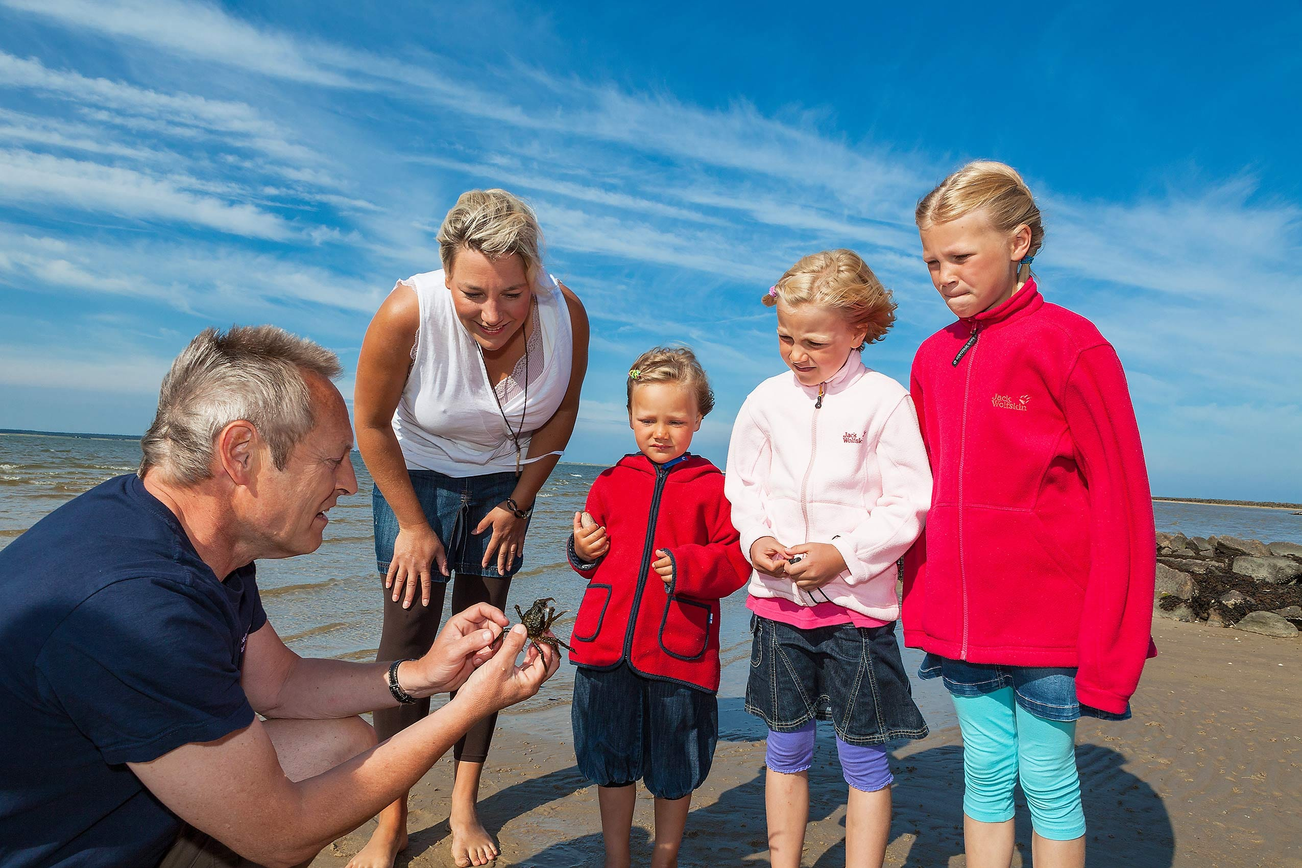 Famiien am Meer betrachtet Krebs