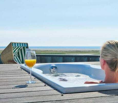 Frau liegt auf der Terasse in der Badewanne und genießt die Aussicht_AmbassadorHotel&Spa_St.PeterOrding