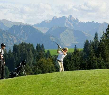Pärchen beim Golfurlaub im Sommer vor den bayerischen Alpen_Sonnenalp_Resort_Ofterschwang