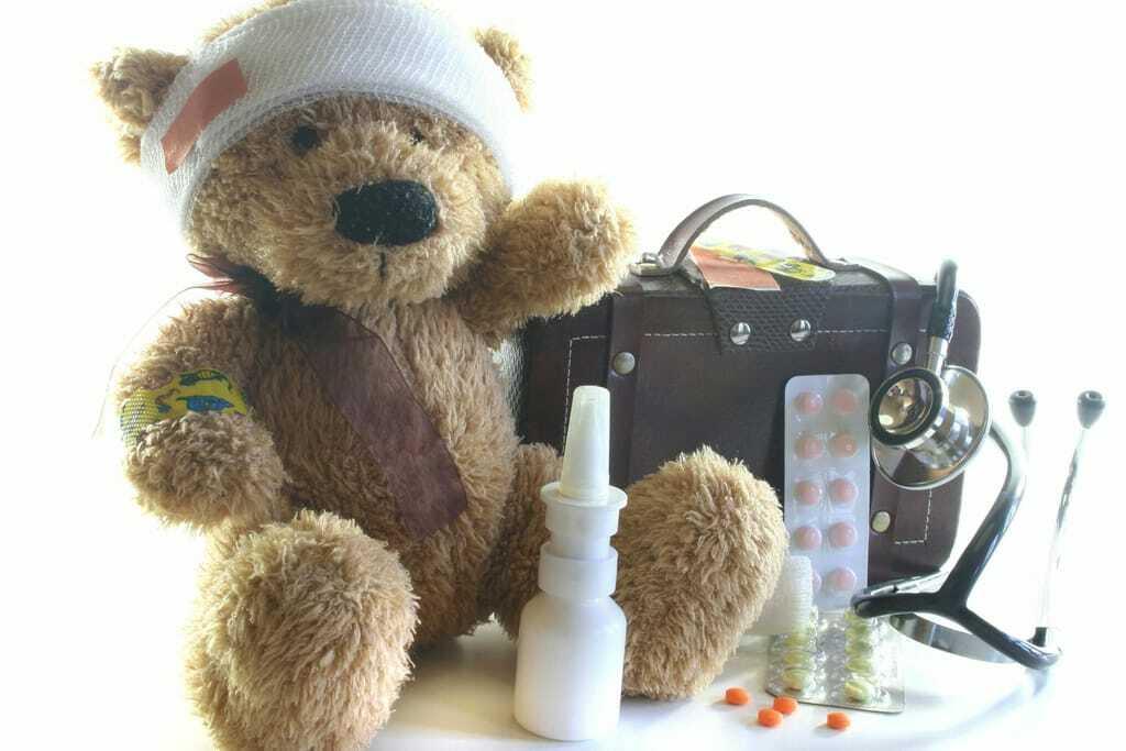 Teddybär mit Verband, daneben Reiseapotheke