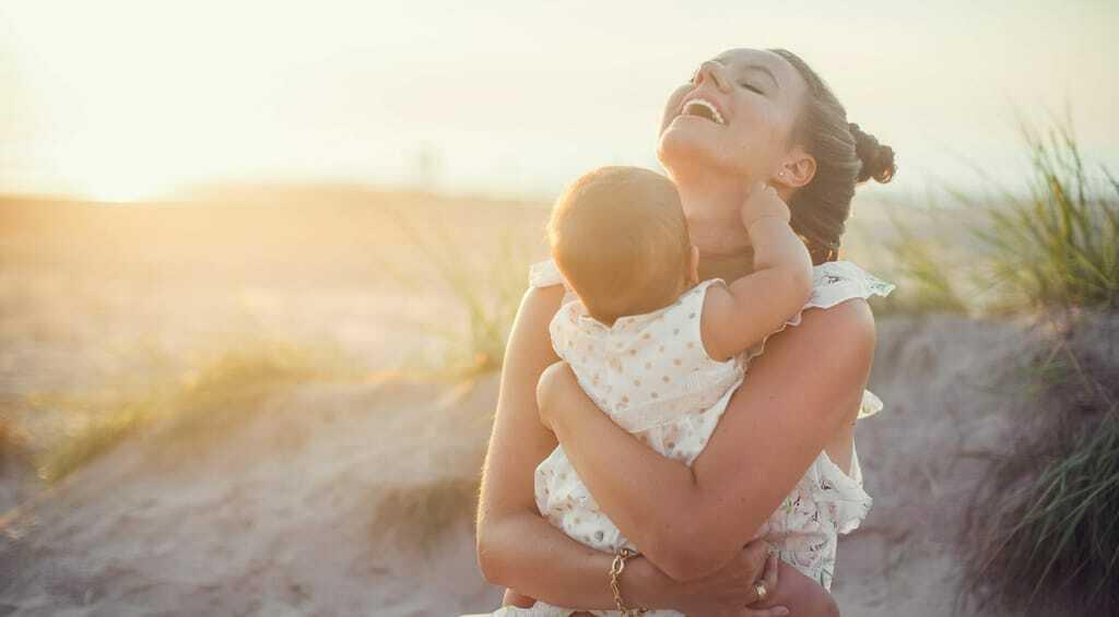 Junge Frau am Strand mit Baby auf dem Arm