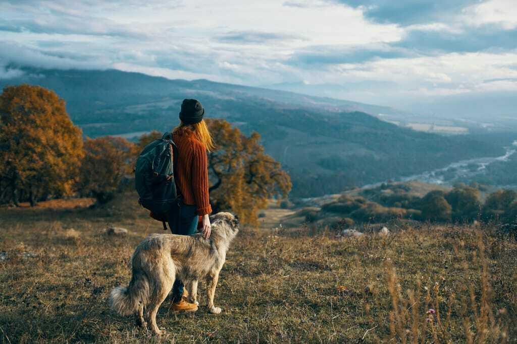 Frau mit weißen Hund blickt über die Berge_Wandern mit Hund
