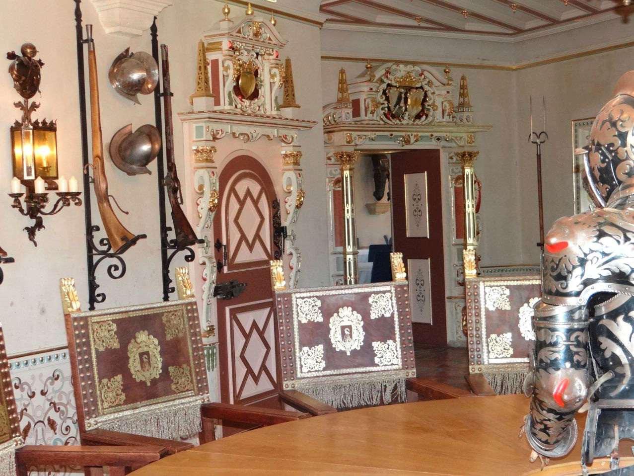 Im Waffensaal stehen Holzstühle mit Blattgoldverzierung