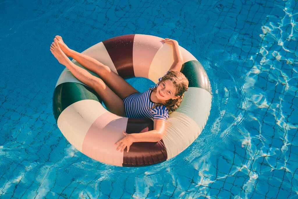 Mädchen sitzt in einem Schwimmreifen im Pool