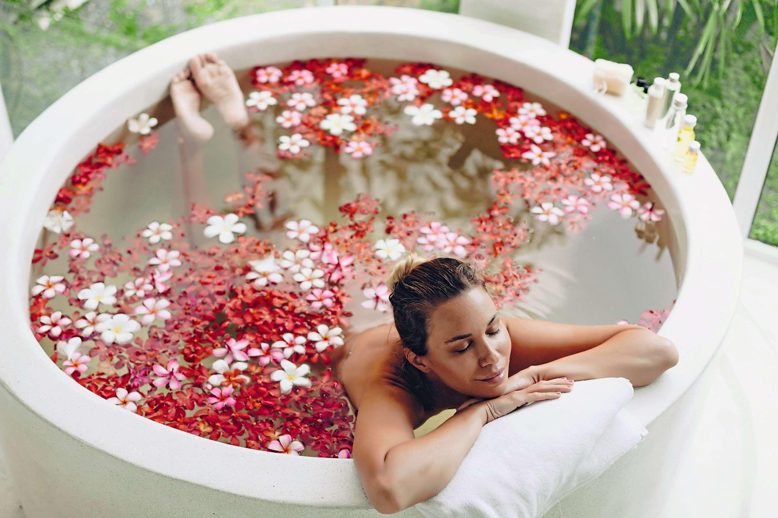 Symbolbild Wellnessurlaub: Frau liegt in einer Badewanne mit Blumen