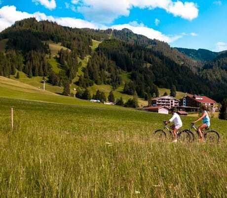 Fahrradweg mit zwei Personen und Hotel im Hintergrund