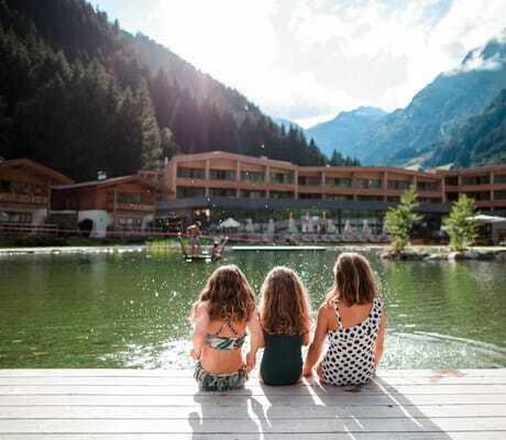 drei kleine Mädchen sitzen am Naturbecken_Feuerstein_Gossensass
