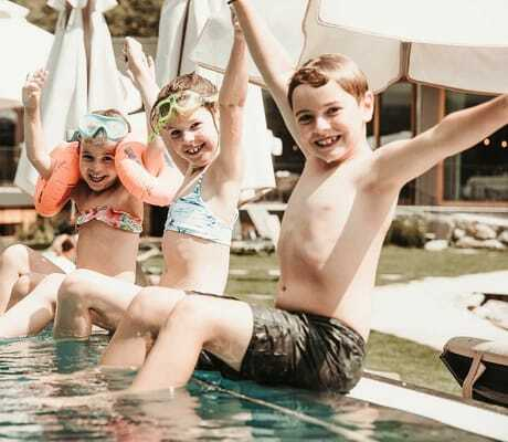 drei Kinder sitzen am Pool und freuen sich_Feuerstein_Gossensass