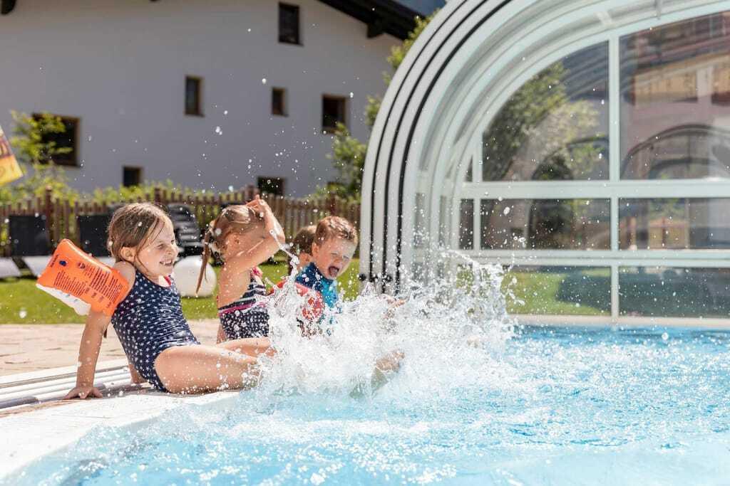 Kinder sitzen am Pool