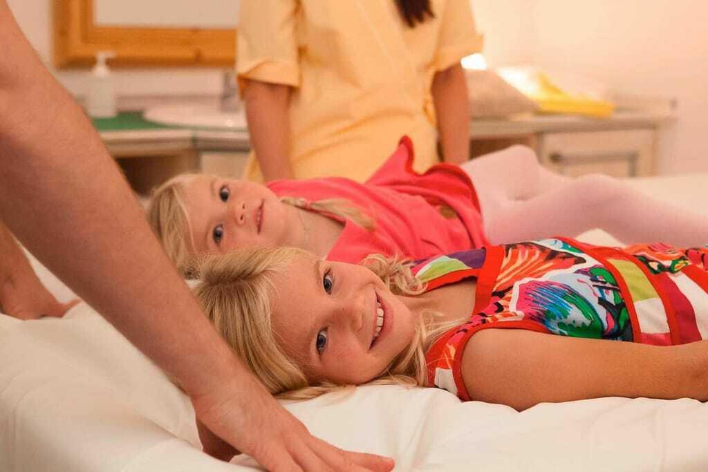 Kinder liegen auf einer Massageliege
