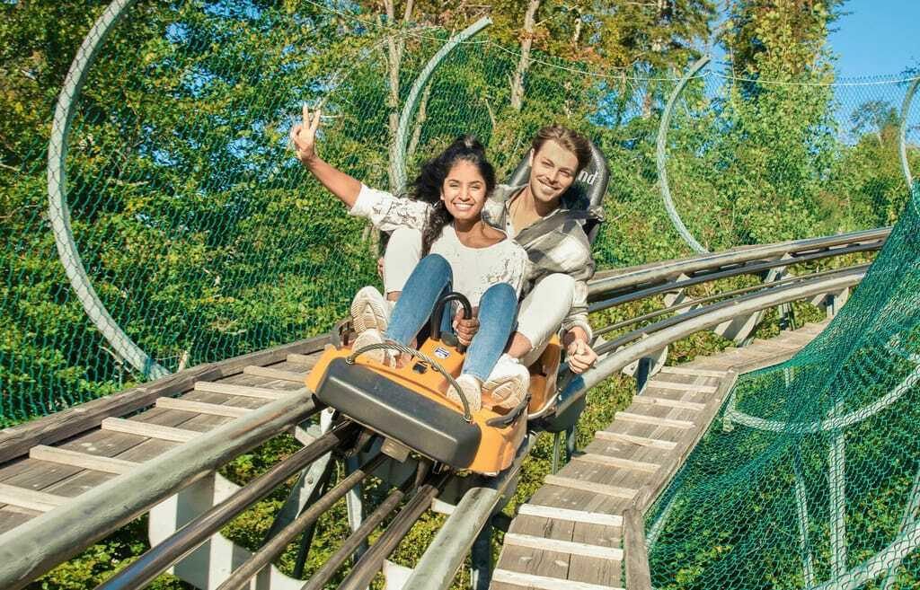 Junges Paar fährt einen Bob im Alpsee Coaster, Frau winkt