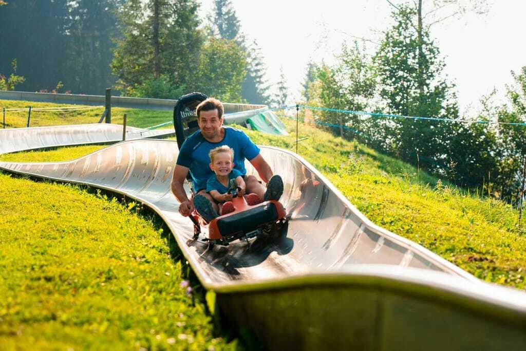 Vater und Sohn haben viel Spaß auf der Sommerrodelbahn Hündle