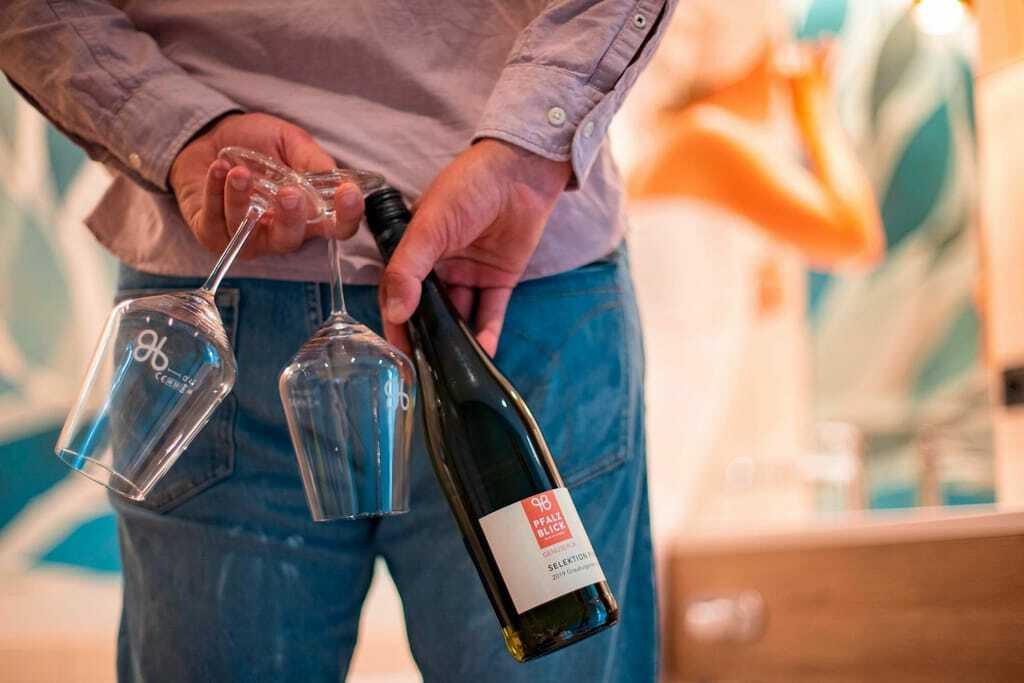 Mann versteckt Weinflasche und Gläser hinter dem Rücken