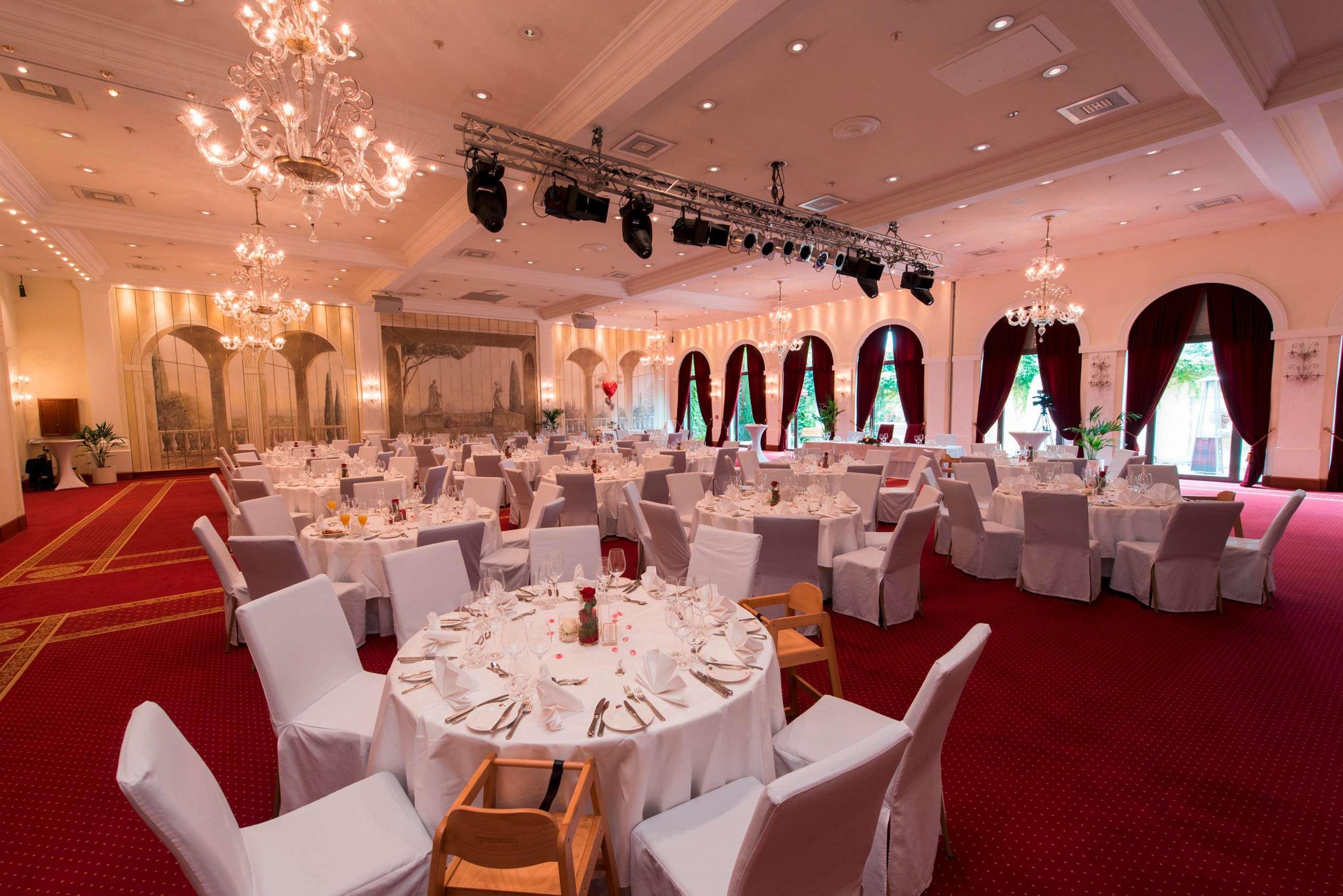 """Der Saal """"La Scala"""" im Hotel Colosseo mit pompösen Kronleuchtern, rotem Teppichboden und großen Bogenfenstern."""