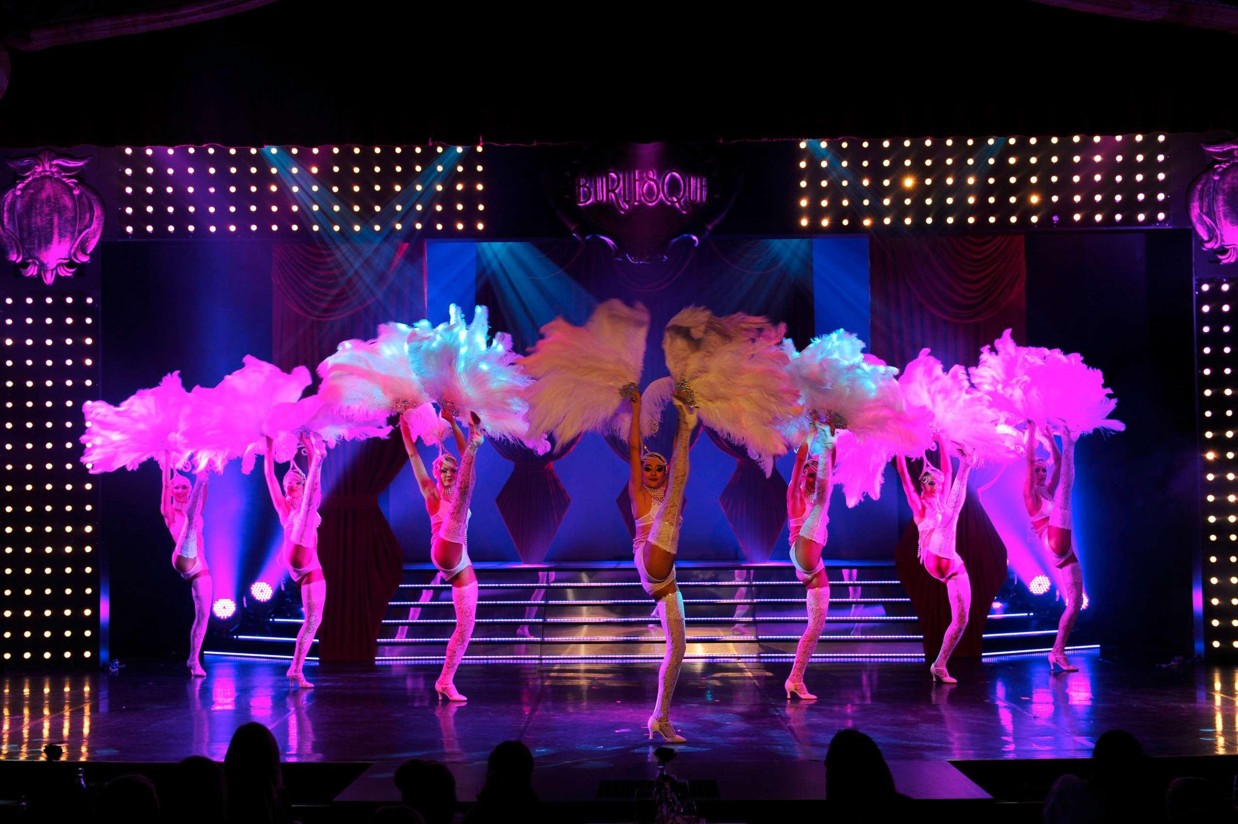 Burlesque Tänzerinnen in weißen Kostümen und mit Federfächern auf einer Bühne.