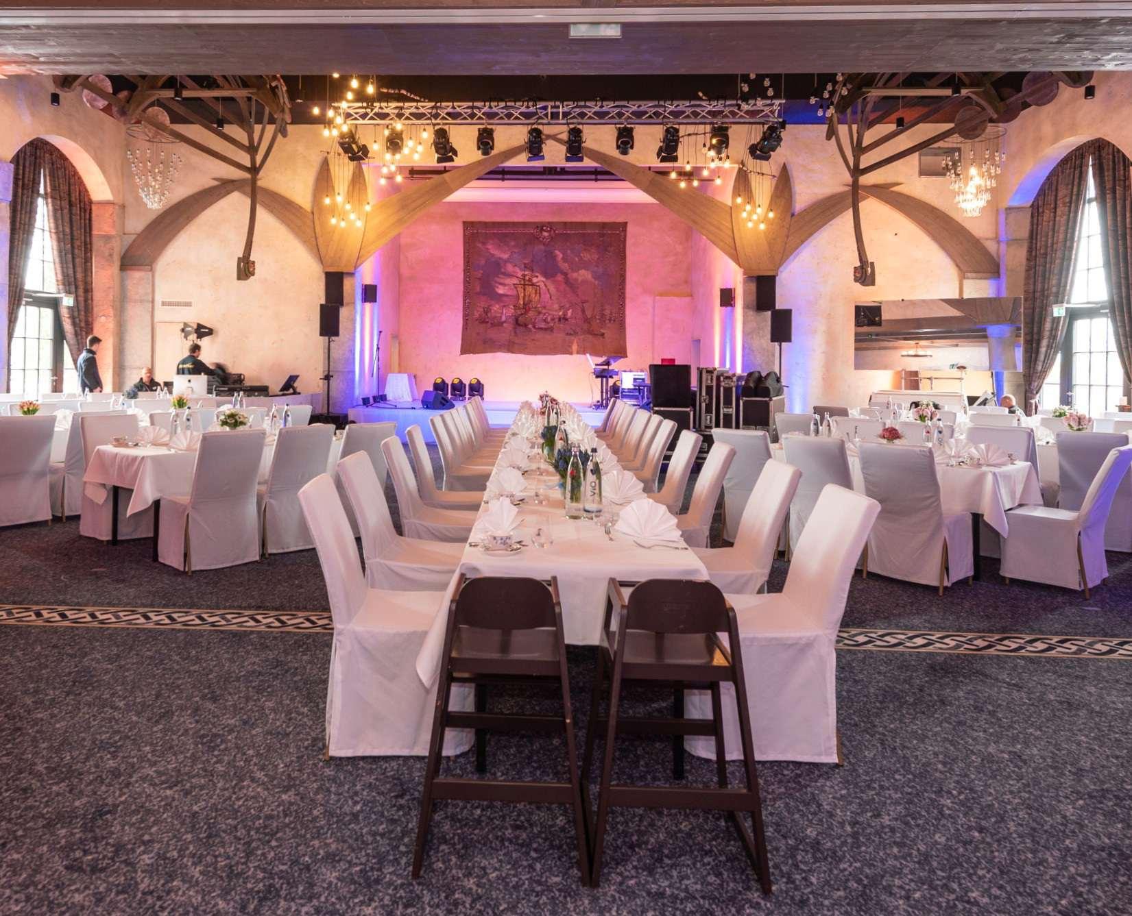 Der im Wikinger-Stil gehaltene Saal Vineta im Hotel Kronasar mit Schiffsskeletten an der Decke und gedeckter Festtafel.