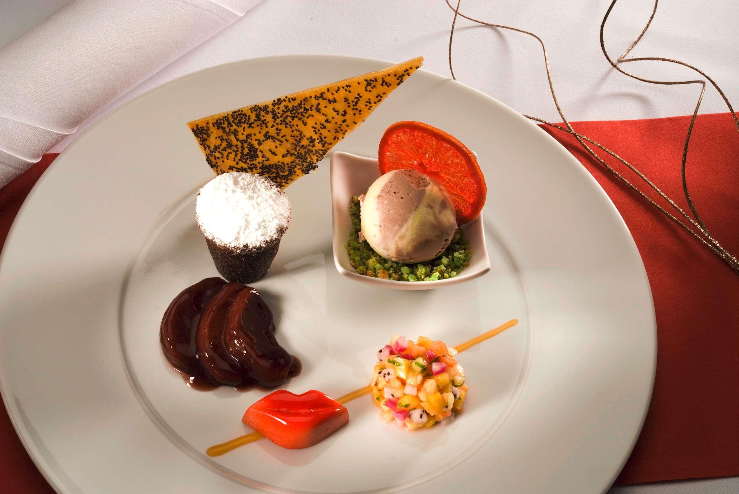 Ein Desserteller mit Eiscreme, Mousse au chocolat und Obstsalat.