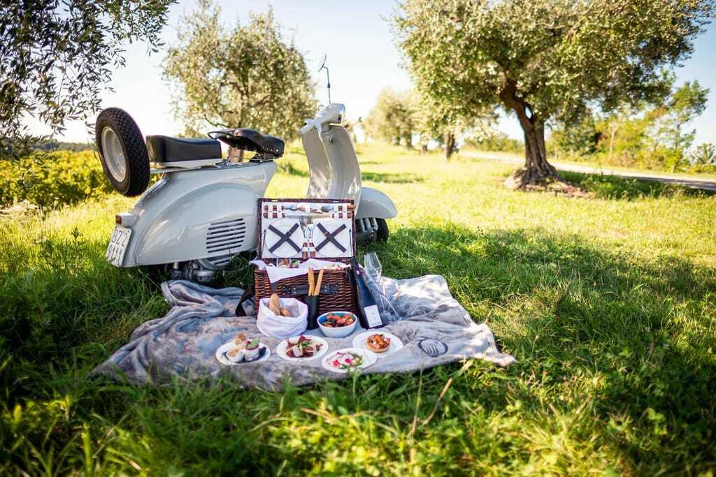 Ein Picknick mit Vespa und feinen Speisen unter Olivenbäumen.