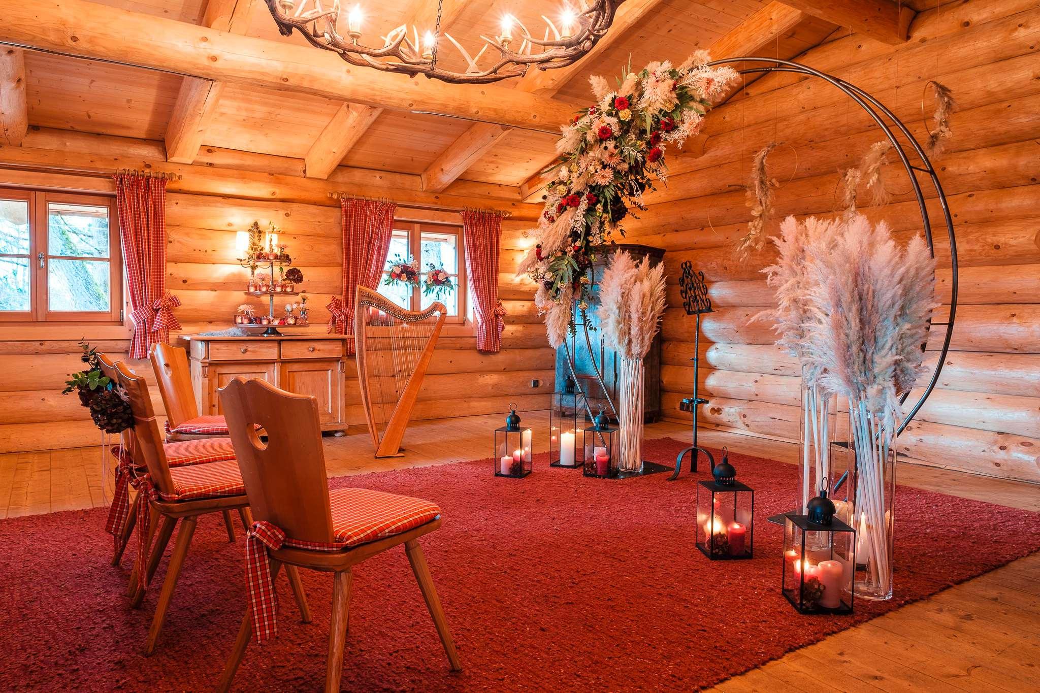 """Der Trauungsraum """"Kleine Alm"""" im Sonnenalp Resort mit einem Blumenbogen, Kerzen und einer Harfe."""