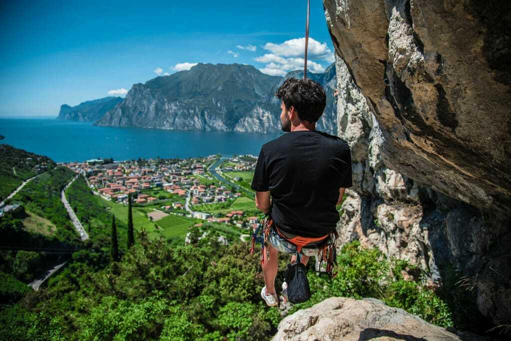 Aktivurlaub am Gardasee: Kletterer hängt hoch über dem See.