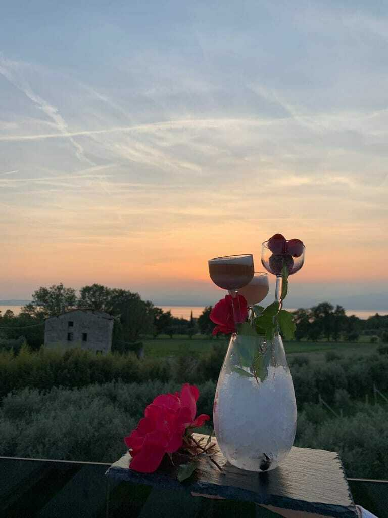 Ein Sektkühler mit Blumen vor einem Sonnenuntergang.