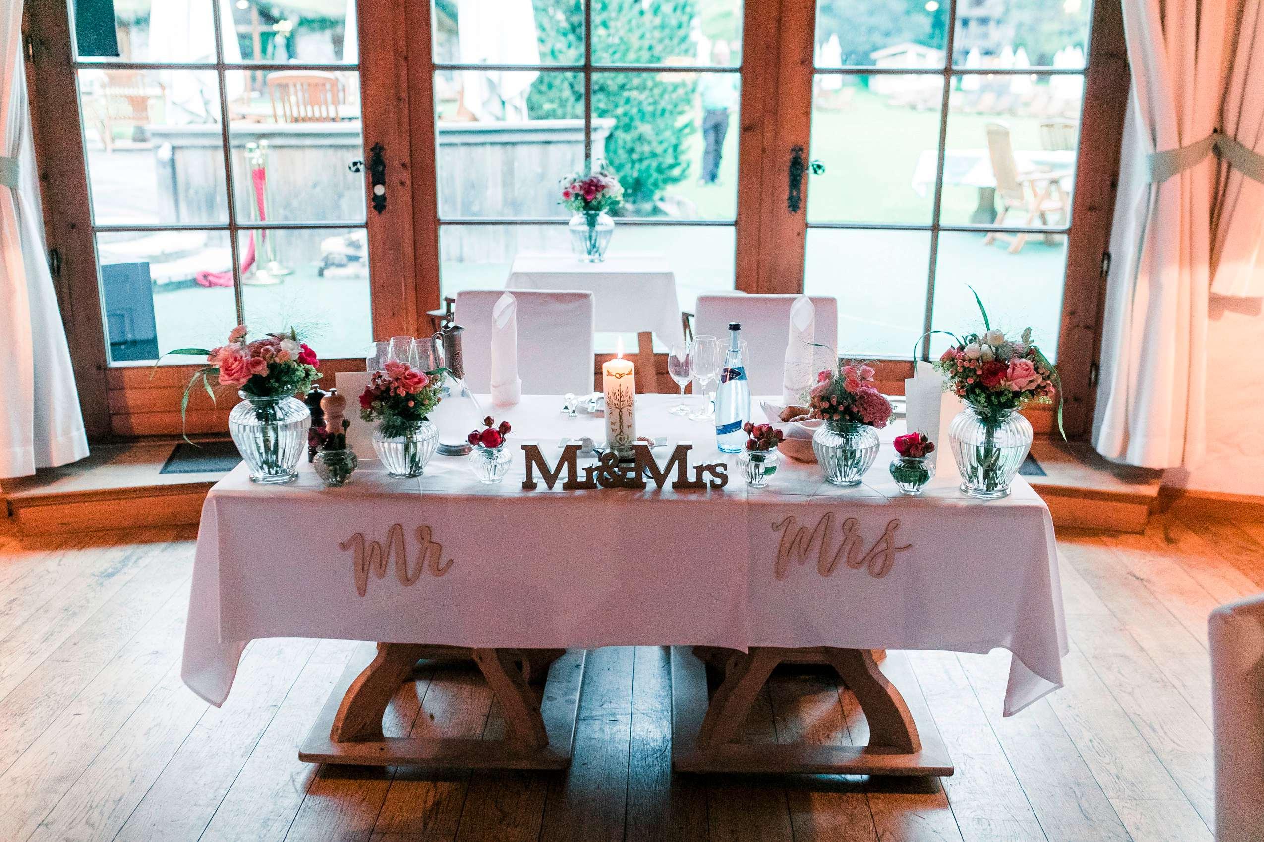 """Brauttisch mit Blumen und """"Mr.&Mrs"""" Schriftzügen."""