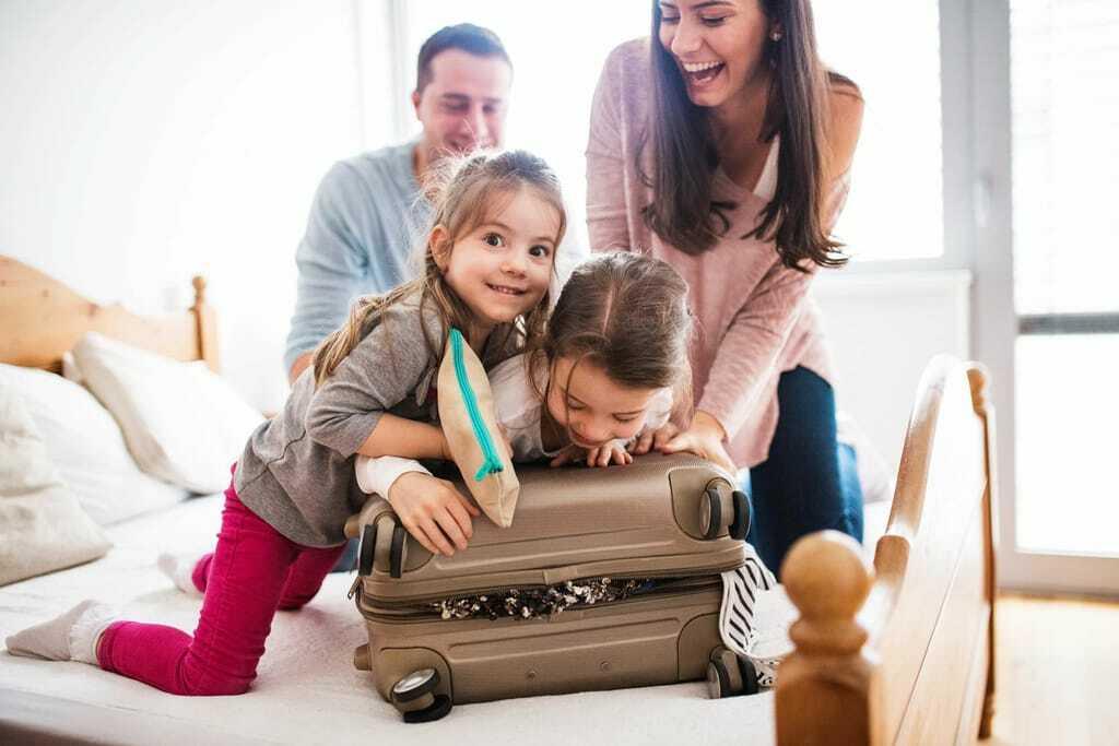 Mama, Papa und zwei Kinder packen fröhlich den Urlaubskoffer für den Familienurlaub