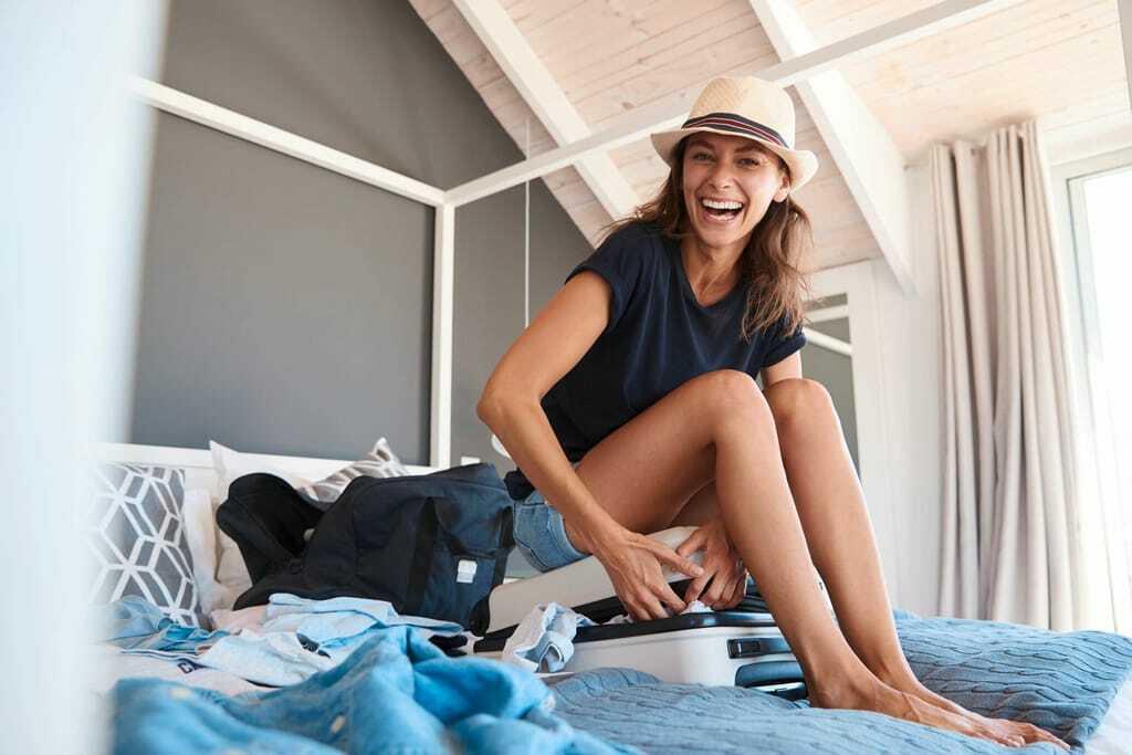 Frau versucht vollen Koffer zu schließen, indem sie sich draufsetzt