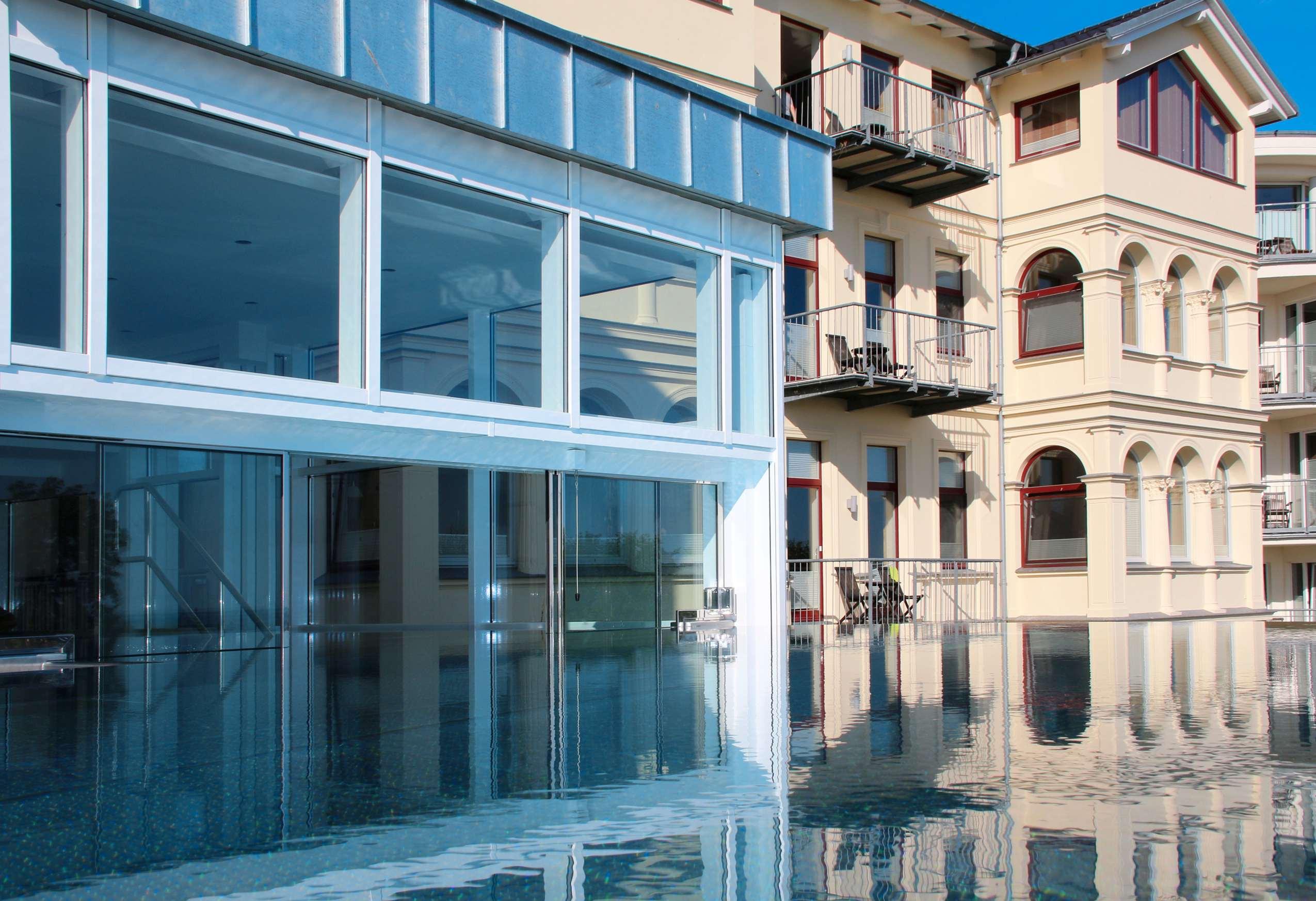 Der Rooftop-Pool des Das Ahlbeck reflektiert das Haus.
