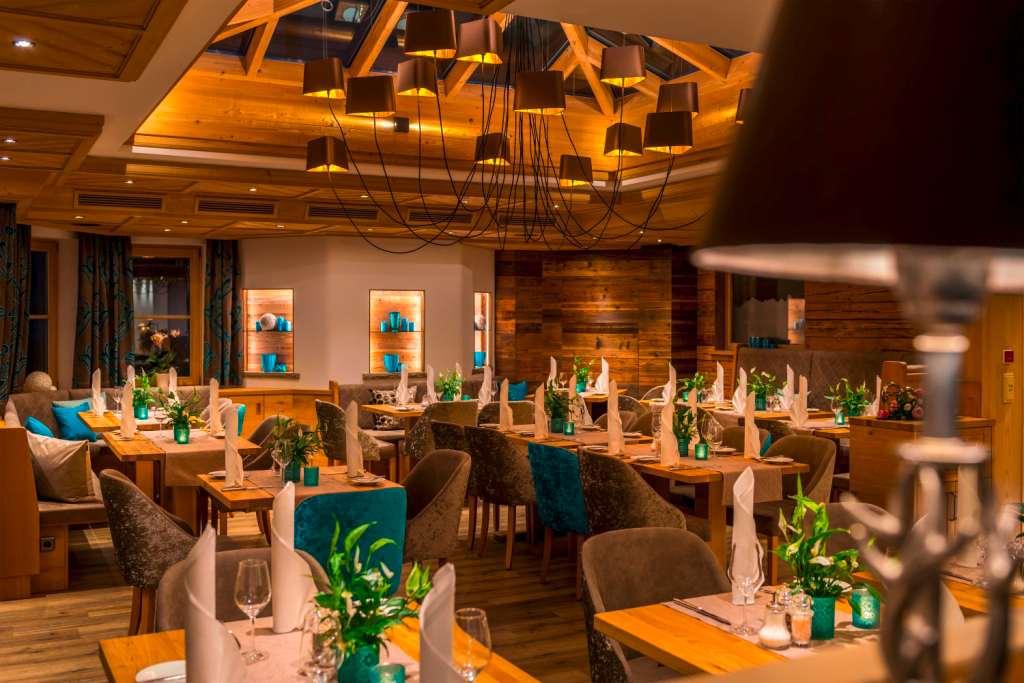 Das Restaurant mit blau-brauner Bestuhlung und Vertäfelten Decken und Wänden.