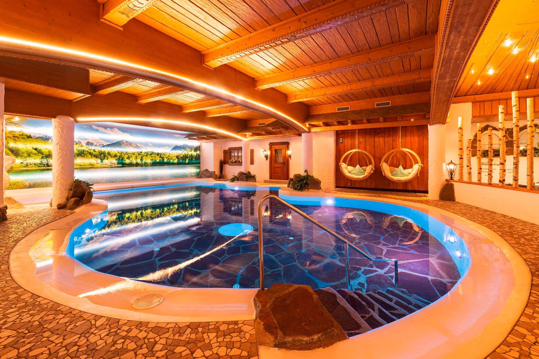 Das Hallenbad mit rundem Pool und hölzernen Decken.