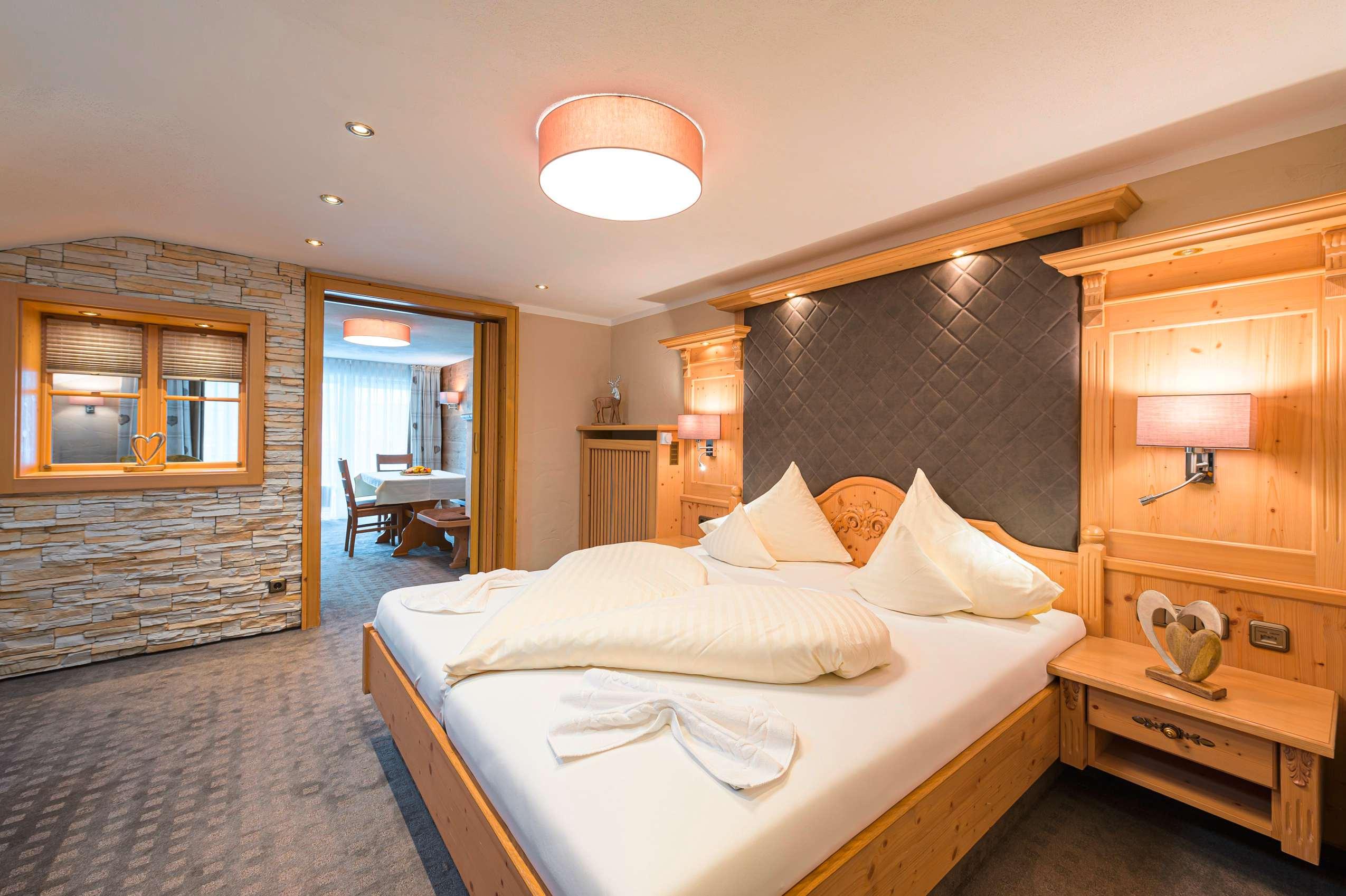 Komfortables Doppelzimmer mit Holzbett und grauen Akzenten