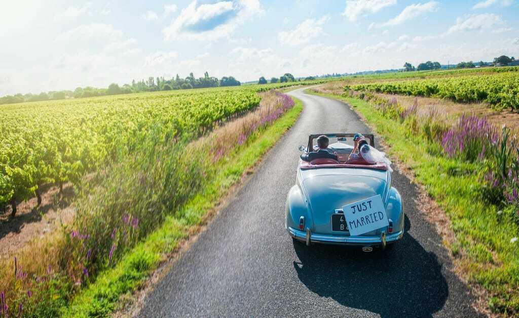 Flitterwochen in Deutschland: Ein frisch vermähltes Paar fährt in einem Oldtimer.