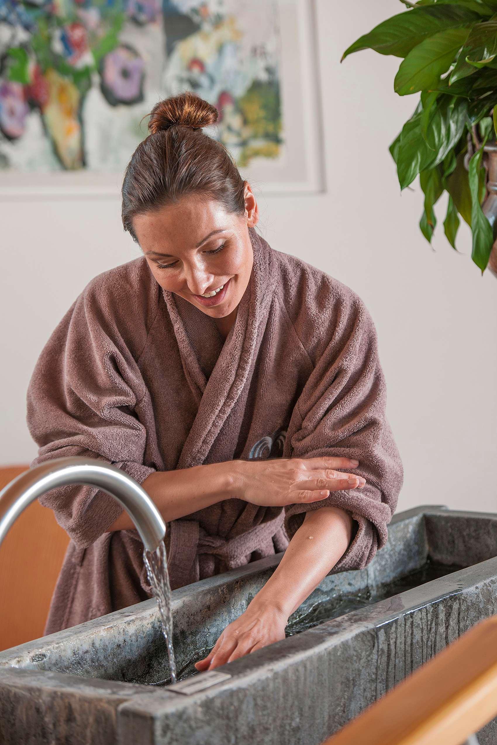 Frau hält Arm in Kneipp-Becken.
